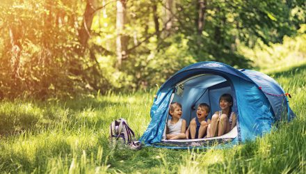 Little girl and brothers are camping in a tent in a sunny forest. Kids aged 5 and 9 are smiling happiliy sitting inside of blue tent. Sunny summer day. Slightly soft.